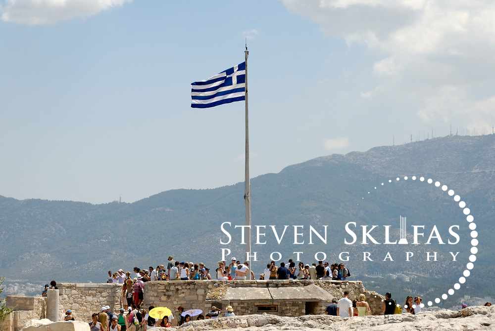 Acropolis. Athens. Greece. View of the Greek National flag flying above the tourist lookout point on the northern corner on top of the Acropolis. The lookout provides panoramic views of the city of Athens including, The Temple of Olympian Zeus, Hadrian's Arch and Lykavittos Hill.