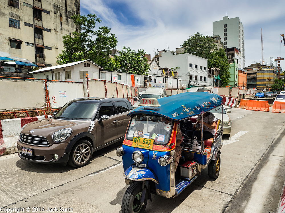 08 JUNE 2016 - BANGKOK, THAILAND:  Traffic drives through some of the subway construction at the intersection of Phlap Phla Chai and Chareon Krung Streets in Bangkok's Chinatown neighborhood. The Bangkok Metropolitan Rapid Transit (MRT) system, Bangkok's subway, is being expanded through Chinatown and a station is under construction at the intersection. The small produce market at the intersection will have to move and several of the businesses near the intersection have been evicted to make way for the construction. Bangkok's Chinatown, considered by some to be one of the best preserved Chinatown districts in the world, is changing. Many of the old shophouses are being demolished and replaced by malls and condominium developments.     PHOTO BY JACK KURTZ
