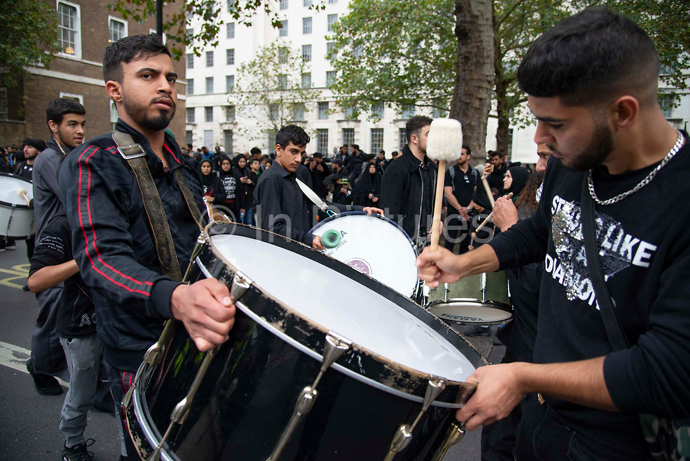 Devote Shia Muslims play large drums , or tabl, which were used in battle to alert the public, disorient the enemy and direct troops during commemorations at the festival of Ashura in Whitehall, London, United Kingdom on 10th Spetember 2019. It marks the day that Husayn ibn Ali, the grandson of the Islamic prophet Muhammad, was martyred in the Battle of Karbala. Ashura is the tenth day of Muharram, the first month in the Islamic calendar.
