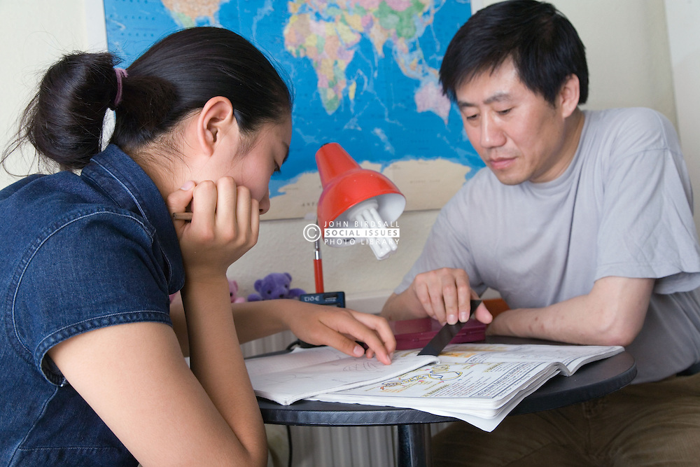 Teenage girl being helped by her father with her homework,