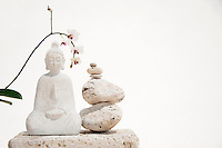 White buddha carving with white orchid flowers and white balanced stones. White Buddha White buddha wood statue with orchid  flowers and balanced stones. Still Life Photography. White buddha wood statue with orchid  flowers and balanced stones.