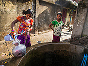 10 NOVEMBER 2014 - SITTWE, MYANMAR: Girls draw water from a communal well in the market in Sittwe, Myanmar. Most neighborhoods in Sittwe rely on well water. Sittwe is a small town in the Myanmar state of Rakhine, on the Bay of Bengal.    PHOTO BY JACK KURTZ