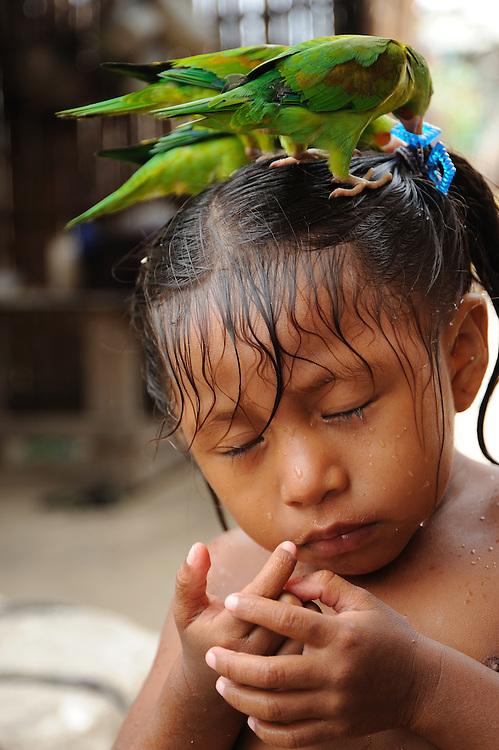 Indígenas guna / comarca de Guna Yala, Panamá.<br /> <br /> Niña indígena con loros sobre la cabeza.