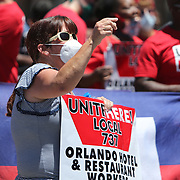 Protestors demonstrate about the Florida unemployment debacle as Florida Governor Ron DeSantis discusses how to safely reopen Florida salons with small business owners during a roundtable at OhSoooJazzy Hair Salon in Orlando, Florida on Saturday, May 2, 2020. (Alex Menendez via AP)