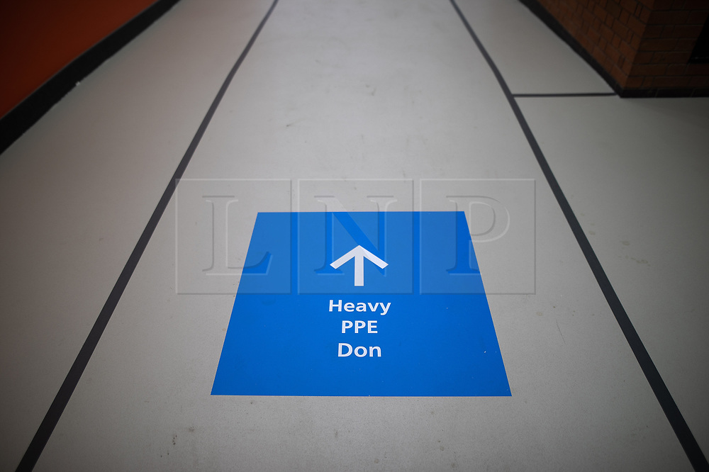 © Licensed to London News Pictures. 12/04/2020. Manchester, UK. Heavy PPE don signs on the floor . The National Health Service is building a 648 bed field hospital for the treatment of Covid-19 patients , at the historical railway station terminus which now forms the main hall of the Manchester Central Convention Centre . The facility is due to open on Easter Monday , 13th April 2020 , and will treat patients from across the North West of England , providing them with general medical care and oxygen therapy after discharge from Intensive Care Units . Photo credit: Joel Goodman/LNP