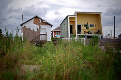 29 August 2014. Lower 9th Ward, New Orleans, Louisiana. <br /> A Brad Pitt inspired 'Make it Right' house stands next to an unfinished private residence  in the Lower 9th Ward on the 9th anniversary of hurricane Katrina.<br /> Photo; Charlie Varley/varleypix.com