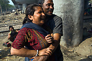 Monu and Seema flirt and play on a piece of waste ground beneath a flyover near Okhla station. New Delhi, India.