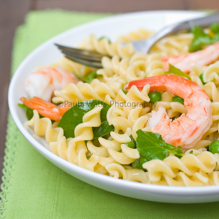 Close up of Colorful seafood pasta salad with fresh herbs in outdoor setting