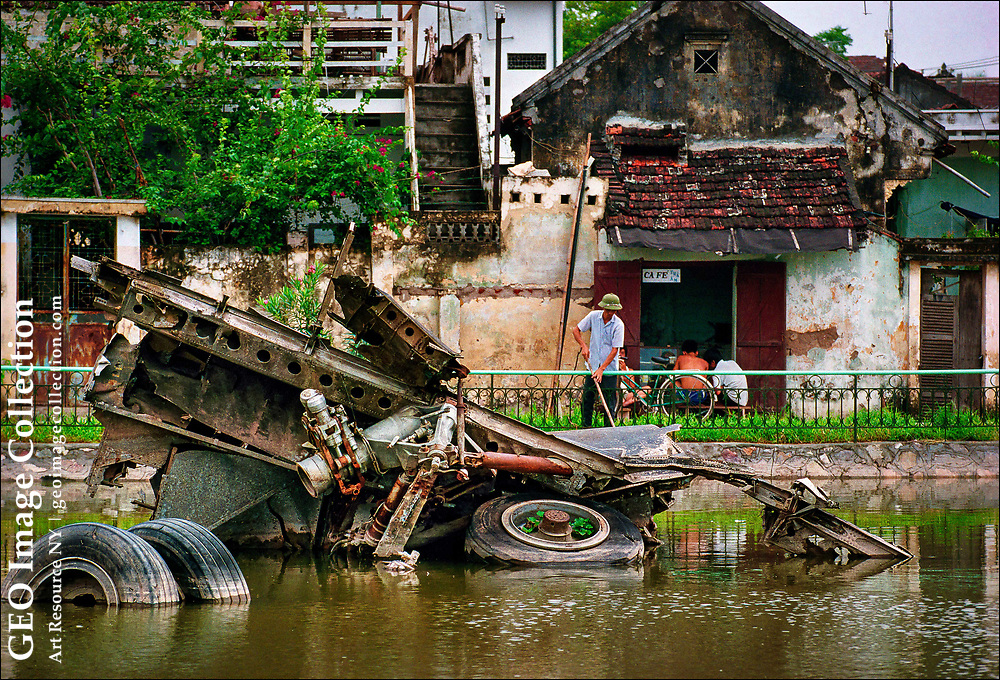 """The wreckage of a U.S. Air Force B-52 bomber, shot down on December 27, 1972, rests half submerged in the algae-green waters of Huu Tiep Lake in a Hanoi neighborhood.  Among older adults, memories linger of the punishing 11-day """"Christmas Bombing"""" of Hanoi and Haiphong, which brought Vietnamese negotiators back to the Paris peace talks and resulted in an agreement to withdrawal all U.S. combat troops from Vietnam."""