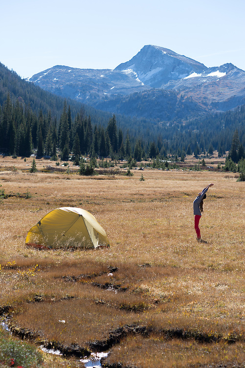 Woman doing yoga at her camp on a backpack trip in Oregon's Wallowa Mountains.