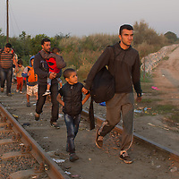Illegal migrants pass an opening on the railway tracks at the razor wire fence on the border between Hungary and Serbia near Roszke (about 174 km South of capital city Budapest), Hungary on September 01, 2015. ATTILA VOLGYI