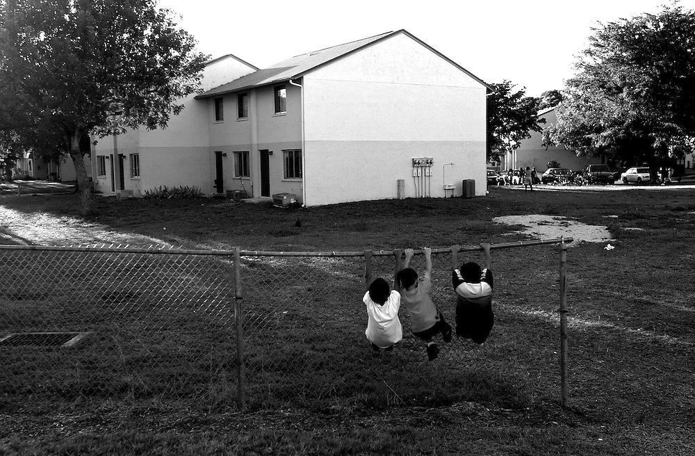 Jose Vega, 9, from left, Jonathan Perez, 7, and Vega's brother, Michael Rodriguez, 6, hang on the fence surrounding the George Washington Carver Apartments in River Park — one of several low-income complexes in the area. A proposed sale of the apartments is a recurring issue, raising questions about the longevity of subsidized housing contracts. Such a sale could change the face of the community and displace hundreds of families.