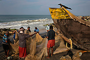 Fishermen on the beach inspecting their mornings catch on 28th February 2018 in Varkala , Kerala, India. With over 30 villagers hauling the nets for 3 hours the catch was very poor and was full of plastic refuse.