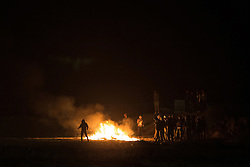 "© Licensed to London News Pictures . 23/10/2016 . Calais , France . A man with a slingshot throws rocks at riot police at the Calais migrant camp known as "" The Jungle "" , in Northern France , on the evening before the start of the eviction and destruction of the camp . Photo credit: Joel Goodman/LNP"