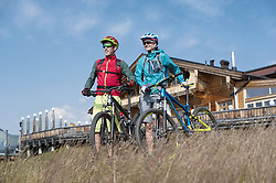 Young couple of mountain bikers standing in alpine landscape and looking at view, Zillertal, Tyrol, Austria
