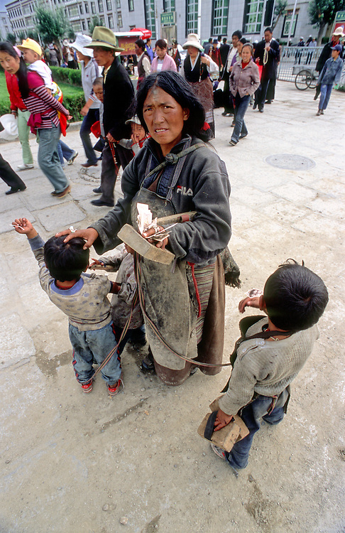 A Tibetan Mother makes a pilgrimage to Lhasa, her children are tied to her by rope, the family wear wooden blocks on their hands  to protect themselves when they lie down on the floor to prostrate. 2005.