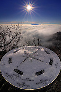 Repeated shapes and concepts in the ground and the sky, with the tourist compass and the rising sun's star in the background. Taken from atop the Mount Pirchiriano in Susa valley, Piedmont, Italy, on a very cold morning at the beginning of December.