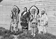 9305-B7384-3. Indians at end of Celilo's new Long House, Feast of The First Salmon, Celilo Village, April 16, 1939. Left to right: Chief Tommy Thompson, Henry Thompson, Chief Nipo T. Strongheart (1891-1966. acted in Hollywood movies and served as a technical advisor about Native Americans), Chief Joe Charley (Yakama) on right.