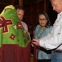 Judges of the art show at the Red Rock State Park Exhibit Hall admire the work of the best of show winner, Tahnibaa Naataanii's shawl Sunday afternoon to start of the 97th Gallup Inter-Tribal Indian Ceremonial.
