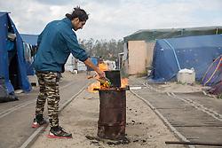 """Calais, Pas-de-Calais, France - 16.10.2016    <br />     <br />  A refugee from parkistan boil water. """"Jungle"""" refugee camp on the outskirts of the French city of Calais. Many thousands of migrants and refugees are waiting in some cases for years in the port city in the hope of being able to cross the English Channel to Britain. French authorities announced that they will shortly evict the camp where currently up to up to 10,000 people live.<br /> <br /> Ein Fluechtling aus Parkistan kocht Wasser. """"Jungle"""" Fluechtlingscamp am Rande der franzoesischen Stadt Calais. Viele tausend Migranten und Fluechtlinge harren teilweise seit Jahren in der Hafenstadt aus in der Hoffnung den Aermelkanal nach Großbritannien ueberqueren zu koennen. Die franzoesischen Behoerden kuendigten an, dass sie das Camp, indem derzeit bis zu bis zu 10.000 Menschen leben Kürze raeumen werden. <br /> <br /> Photo: Bjoern Kietzmann"""