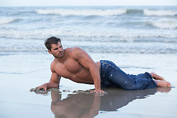 muscular man in wet jeans on the shore at the beach