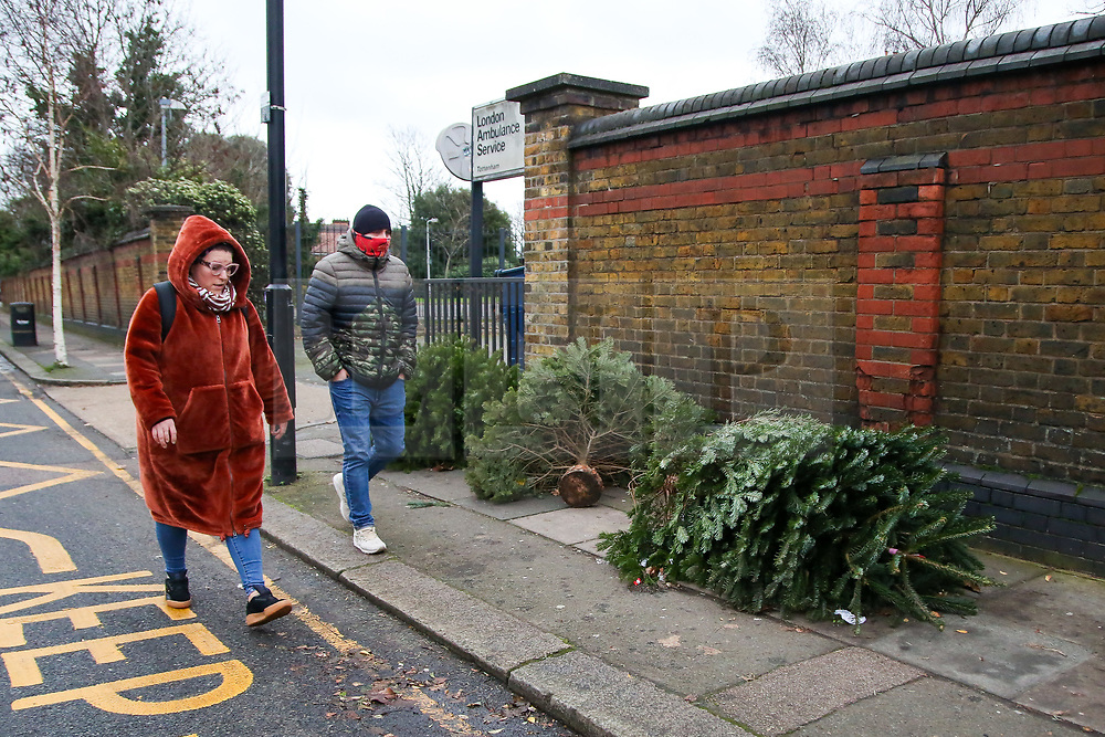 © Licensed to London News Pictures. 26/12/2020. London, UK. A couple walk past a line of discarded Christmas trees on a pavement in Haringey, north London on Boxing Day. Traditionally Christmas decorations including the tree are taken down on Twelfth Night after Christmas Day. Photo credit: Dinendra Haria/LNP