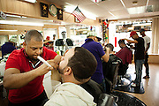 ALLENTOWN, PA – JUNE 4, 2011: Ernesto Perres carefully shaves the face of a client at  Manhattan Barber Shop in Allentown, Pennsylvania. The shop is one of dozens of Latino owned business lining Allentown's 7th Street, where Perres, an immigrant from Domincan Republic, has worked for more than nine years.<br /> <br /> As the population of second and third generation Hispanics increases dramatically in the United States, a new boldness can be sensed among Latinos in America, stretching far beyond the southern border states. Demographers in Pennsylvania say the towns of Bethlehem, Allentown and Reading are set to become majority-minority cities, where Hispanics comprise a bigger portion of the population than whites. As this minority population increases dramatically in the region, Latinos are inching closer to their own realization of the American Dream, while gradually shifting the physical and cultural landscapes of their communities.