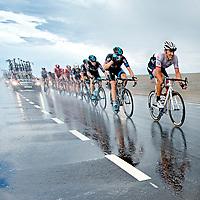 Nederland, Brouwersdam, 05-07-2015.<br /> Wielrennen, Tour de France.<br /> Etappe van Utrecht naar Neeltje Jans.<br /> Fabian Cancellara geheel rechts in de eerste groep op een kletsnatte Brouwersdam.<br /> Foto: Klaas Jan van der Weij