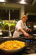 Dolly Irigoyen frying slices of apples in a frying pan, and frying slices of black blood sausage. The Dolly Irigoyen - famous chef and TV presenter - private restaurant, Buenos Aires Argentina, South America Espacio Dolli