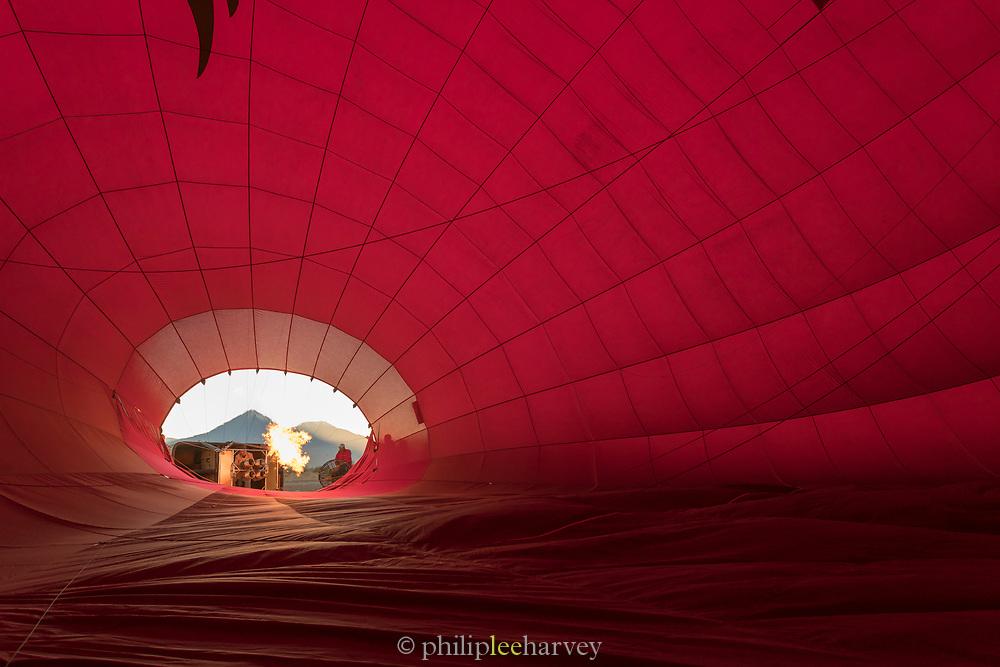 Man preparing hot air balloon to start his adventure, view from inside balloon, Atacama Desert, Chile