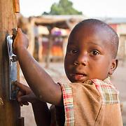 Ever experimental, little Djibi plays with a door handle. Koumbadiouma, Kolda, Senegal.