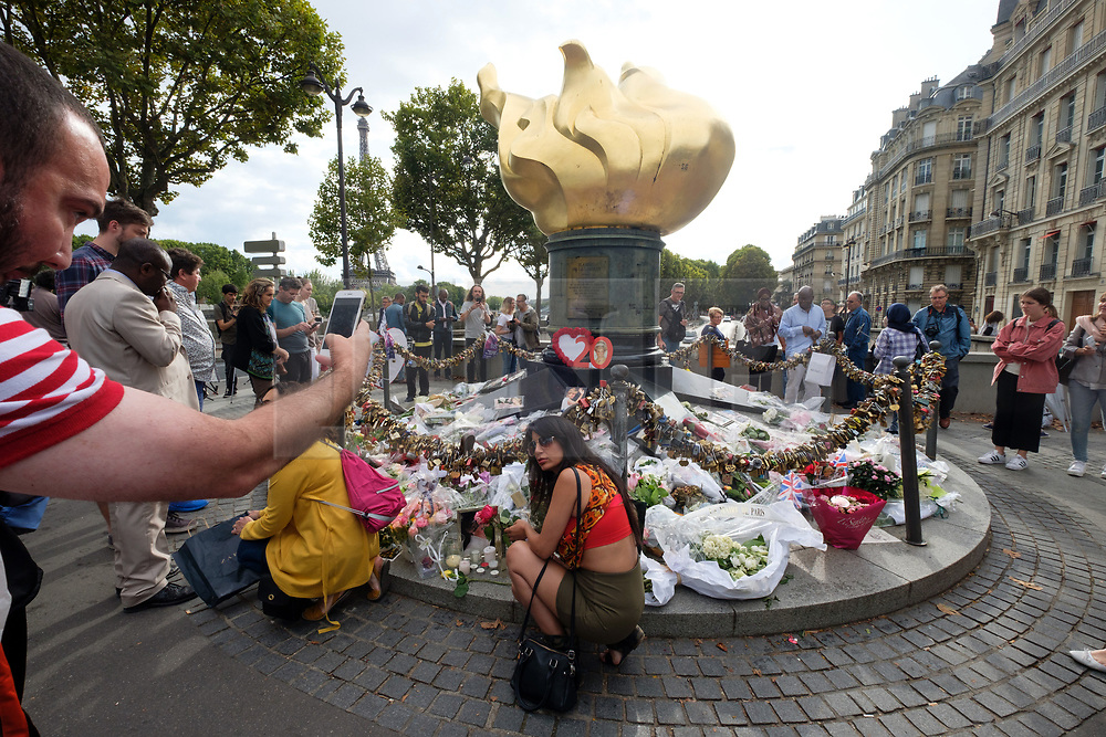 © Licensed to London News Pictures. 31/08/2017. Paris, France. A man take a photo with his mobile phone of a woman posed next to tributes to the late Princess Diana above the Post de l'Alma tunnel in Paris.  Princess Diana died with Dodi Al-Fayed in a car crash on 31st August 1997. Photo credit: Ray Tang/LNP
