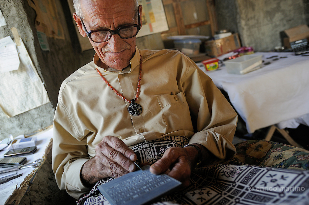 """Northeastern Anatolia. Near Cavustepe, the Urartian fortress-city Sardurihinli, Mehmet Kusman engraving black stones with Urartian cuneiforms and Arabic phrases. Mustafa, known locally as """"Urartu Mehmet"""", first came to the Urartian ruins in 1963, at the age of 23, to work as a security guard at the new archaeological site.<br /> For 10 years he watched the archaeologists until someone unearthed Urartian cuneiforms, engraved into the rocks. Mustafa learned all he could about this ancient language and from 1993 started giving presentations on the subject."""