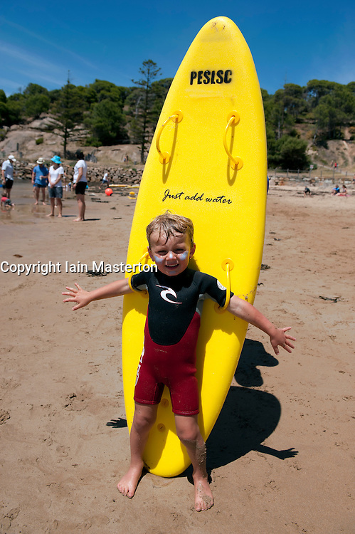 Young boy holding yellow surf board on beach in Adelaide Australia