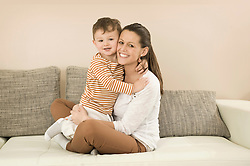 Portrait of mother and son sitting on sofa, smiling