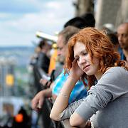 Sad girl among tourists on Eiffel Tower. Loneliness, misunderstanding