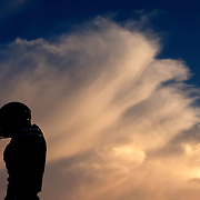A St. Francis football player stands in front as the sunset illuminates a billowing cloud during a high school football game between St. Francis de Sales and Anthony Wayne at the University of Toledo's Glass Bowl in Toledo on Friday, Sept. 13, 2019. THE BLADE/KURT STEISS<br /> SPT SFAWfootball14p