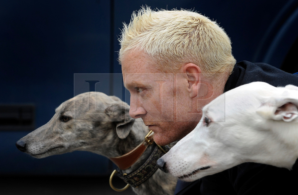 ©London News pictures. 17.02.2011. Iwan Thomas (C) with greyhounds Cindy (L) and Tom (R).  Iwan Thomas joins the Retired Greyhound Trust (RGT) today (Thurs) at Wimbledon Stadium to highlight the plight of thousands of retired dogs needing homes. The trust currently has 1,000 dogs needing homes and a further 4,000 expected this year. The dogs only need two 20min walks a day Greyhound UK has teamed up with the RGT as its charity for the for the year. Picture Credit should read Stephen Simpson/LNP