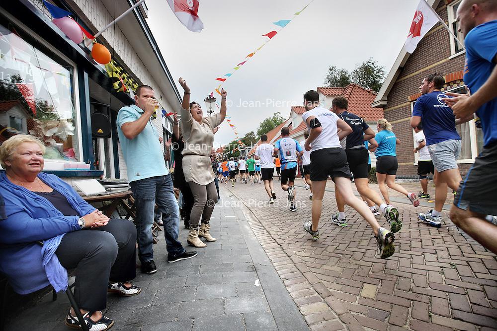 Nederland, Amsterdam , 22 september 2013.<br /> Dam tot Dam loop 2013.<br /> Deelnemers lopen over de Landsmeerderdijk in Amsterdam Noord, aangemoedigd door bewoners.<br /> Foto:Jean-Pierre Jans