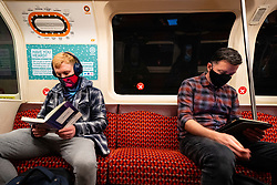 Glasgow, Scotland, UK. 25 September, 2020. As the threat of a second wave of Covid-19 cases increases , members of the public go about their business in Glasgow city centre today.  Pictured;  Two men reading at a social distance on the Glasgow subway system. Iain Masterton/Alamy Live News