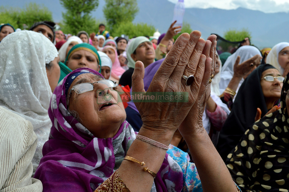 April 25, 2017 - Srinagar, Jammu and Kashmir, India - An elderly Kashmiri Muslim women devotee prays as a head priest displays a holy relic believed to be the hair from the beard of Prophet Mohammad, on Mehraj-u-Alam at the Hazratbal Shrine on the outskirts of Srinagar, India, Tuesday, April 25, 2017. Mehraj-u-Alam is believed to mark the ascension of Prophet Mohammad to heaven. (Credit Image: © Zahid Bhat/Pacific Press via ZUMA Wire)