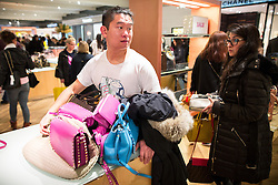 © Licensed to London News Pictures . 26/12/2015 . Manchester , UK . A man hoarding several handbags as other shoppers try to pick them up , at the Selfridges winter sale . Photo credit: Joel Goodman/LNP
