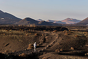 A woman walks across a volcanic landscape  on 25th November 2020 in Los Volcanes Natural Park in Lanzarote, Spain. The island was transformed by huge volcanic eruptions from 1731-36, which give it its unique dramatic landscape, and created the area now known as Timanfaya Natural Park, seen in the distance.