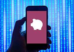 Person holding smart phone with PiggyBank pay-day liana's company   logo displayed on the screen. EDITORIAL USE ONLY