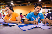 """18 AUGUST 2012 - PHOENIX, AZ:  Young people who hope to win """"deferred action"""" status go over paperwork at a deferred action workshop in Phoenix. More than 1000 people attended a series of 90 minute workshops in Phoenix Saturday on the """"deferred action"""" announced by President Obama in June. Under the plan, young people brought to the US without papers, would under certain circumstances, not be subject to deportation. The plan mirrors some aspects the DREAM Act (acronym for Development, Relief, and Education for Alien Minors), that immigration advocates have sought for years. The workshops were sponsored by No DREAM Deferred Coalition. PHOTO BY JACK KURTZ"""