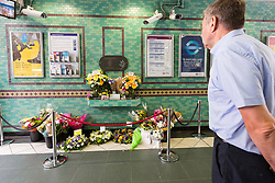 © Licensed to London News Pictures. 07/07/2015. London, UK. A man looks at flowers shortly before people observe a minute silence at Aldgate tube station in London, on the tenth anniversary, for victims of the 7/7 bombings. Photo credit : Vickie Flores/LNP
