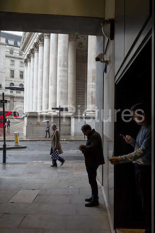 City people shelter from rain in the privacy of a dark corner to check messages, by Cornhill in the City of London, the capitals financial district, 7th March 2018, in London England.