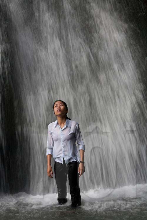 A young Vietnamese girl bathes in the Silver waterfall of Tam Dao, Vietnam, Southeast Asia