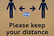A Covid denier's sticker is central to a Coronavirus sign telling travellers to stay apart on a public transport 'Please Your Distance' bus shelter sign, on 20th January 2021, in London, England.