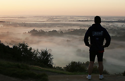 © Licensed to London News Pictures. 28/09/2015. Dorking, UK. A jogger admires the fog covering the landscape south of Box Hill, Surrey as the sun rises.  Photo credit: Peter Macdiarmid/LNP